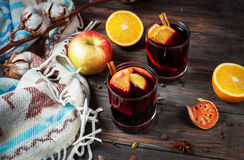 Hot mulled wine with spices, apple and orange on wood Stock Photos