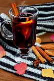 Hot Mulled wine with spices cinamon, star anise and dried lemon on knitted scarf .Fallen leaves. Autumn theme.Selective focus.Vert. Ical shot royalty free stock photography