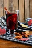 Hot Mulled wine with spices cinamon, star anise and dried lemon on knitted scarf .Fallen leaves. Autumn theme.Selective focus.Vert. Ical shot stock photography