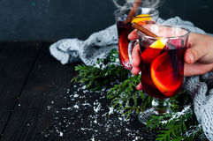 Hot mulled wine with spices in a female hand Royalty Free Stock Photo