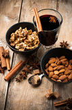 Hot mulled wine, spices and nuts. A glass of hot mulled wine, spices, cinnamon, star anise, brown sugar and nuts on a wooden board Royalty Free Stock Images