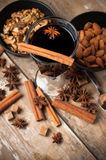 Hot mulled wine, spices and nuts. A glass of hot mulled wine, spices, cinnamon, star anise, brown sugar and nuts on a wooden board Royalty Free Stock Photography