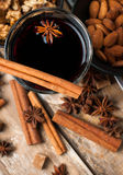 Hot mulled wine, spices and nuts. A glass of hot mulled wine, spices, cinnamon, star anise, brown sugar and nuts on a wooden board Stock Image