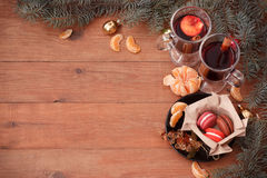 Hot mulled wine, tangerines and spruce branches on a wooden table. Hot mulled wine, tangerines and spruce on a wooden table Stock Image