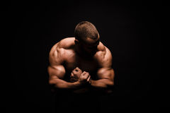 Hot muscular man on a black background. A shirtless bodybuilder showing off triceps and biceps. Hard workout concept. royalty free stock image