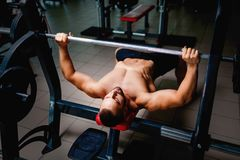 Hot muscular men in a gym on a bench press using a barbell, exercise equipment on a blurred dark background. Men with a hot muscular body with naked torso using royalty free stock images