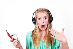 Hot music. Girl listening to hot music from a chili Royalty Free Stock Photo