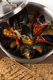 Hot mussels in metal pan with lid on brown napkin Royalty Free Stock Images