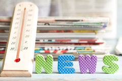 Hot news creative symbol with thermometer and newspaper Royalty Free Stock Image