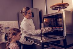 Nice young woman taking a hot tray with muffins royalty free stock images