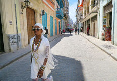 A hot noon in Havana. Cuba, Havana - 07 April, 2016: a young local woman dressed in white and in jewelry is walking down the street on a hot day in Havana, with Stock Photos