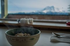 Hot oatmeal in a mountain cabin. Bowl of steaming oatmeal in a mountain cabin by Mt Stock Photo