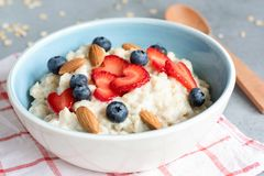 Hot oatmeal porridge with fresh berries and nuts. In a blue bowl, closeup view. Concept of healthy eating, healthy lifestyle, dieting and fitness food Royalty Free Stock Photos
