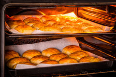 Hot oven with golden buns Royalty Free Stock Photo