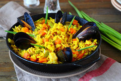 Hot paella with vegetables and mussels Stock Photos