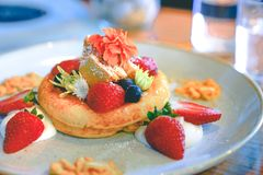 Hot pan cake topped with fresh strawberries , blueberries, honey stock photography