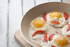 Hot pan with fried eggs and small pieces of tomato Stock Images