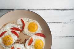Hot pan with fried eggs and small pieces of tomato Stock Photography