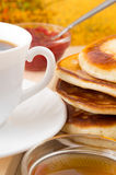 Hot pancake topped with honey and white cup of tea Stock Photography