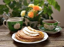 Hot pancakes, fragrant tea and sour cream Stock Images