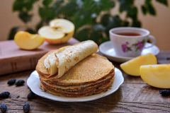 Hot pancakes, fragrant tea and apples Stock Image