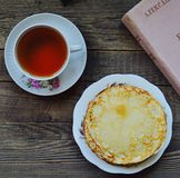 Hot pancakes, fragrant tea and book Royalty Free Stock Photos
