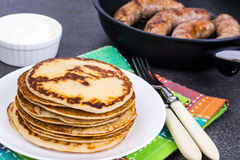 Hot pancakes with homemade sausage in frying pan Royalty Free Stock Image