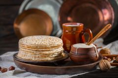 Hot pancakes on a plate with milk and sour cream, carnival, maslenitsa. Image in retro, rustic style stock photo