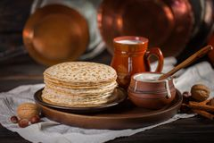 Hot pancakes on a plate with milk and sour cream, carnival, maslenitsa. Image in retro, rustic style stock photos