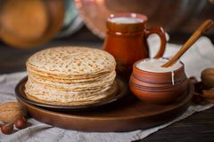 Hot pancakes on a plate with milk and sour cream, carnival, maslenitsa. Image in retro, rustic style royalty free stock images