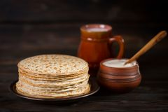 Hot pancakes on a plate with milk and sour cream, carnival, maslenitsa. Image in retro, rustic style royalty free stock photo
