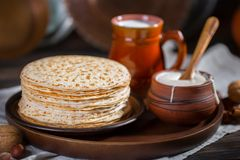 Hot pancakes on a plate with milk and sour cream, carnival, maslenitsa. Image in retro, rustic style royalty free stock image