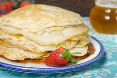Hot pancakes with strawberries on the ceramic plate Royalty Free Stock Photos