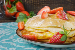 Hot pancakes with strawberries and honey on the ceramic plate Stock Images