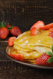 Hot pancakes with strawberries and honey on the ceramic plate Royalty Free Stock Photography