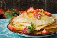 Hot pancakes with strawberries and honey on the ceramic plate Royalty Free Stock Photo