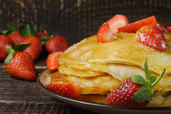 Hot pancakes with strawberries and honey on the ceramic plate Stock Image