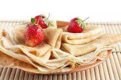 Hot pancakes with strawberries on top. Isolated on white Stock Photo
