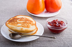 Hot pancakes, strawberry jam and tomatoes close-up Royalty Free Stock Photos