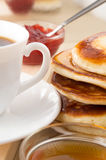 Hot pancakes topped with honey and white cup of tea Stock Images
