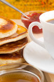 Hot pancakes topped with honey and white cup of tea Royalty Free Stock Photography