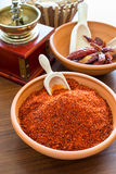 Hot paprika. In ceramic bowl with chillies on background royalty free stock image