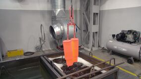 The hot parts are transported from the furnace to the quenching liquid. Quenching of steel billets. Cooling of