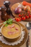 Hot pea soup with smoked meats and vegetable stock image