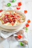 Hot penne bolognese with bacon and herbs Stock Image