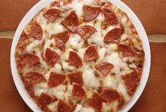 Hot Pepperoni Pizza. Delicious pepperoni and cheese pizza plate on kitchen tile Stock Photo