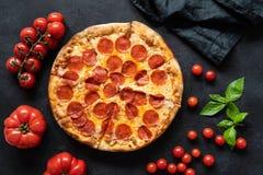 Hot pepperoni pizza on black stone background royalty free stock photo