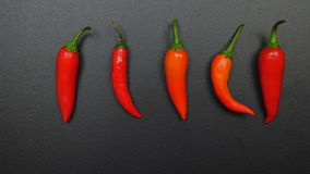 Hot peppers on a black table (stop-motion) stock footage