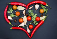 Hot peppers laid out in the shape of a heart with vegetables royalty free stock photography