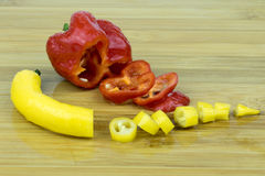 Hot peppers in red and yellow. Closeup of two fresh and crisp, red and yellow very hot chili peppers on a wooden cutting board Stock Photography